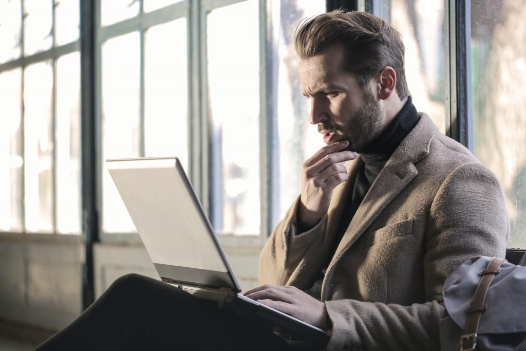 While thinking about the right decision man holding his chin facing laptop computer